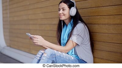 Attractive young woman listening to her music on stereo...