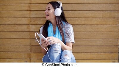 Happy woman enjoying her music - Happy pretty young brunette...