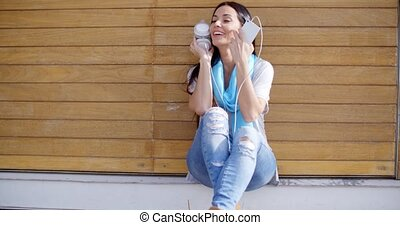 Happy relaxed young woman listening to music