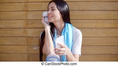 Young woman listening to music on her mobile phone holding...