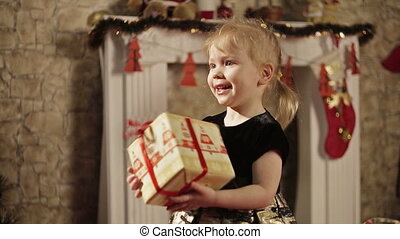 Happy little girl with gift box - Cheerful young girl with...