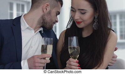 Young happy amorous couple with glasses of champagne on...