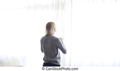 Beauty Girl opens curtains on big window and let the light...