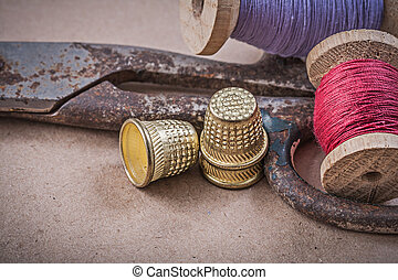 Reels of sewing threads thimbles scissors on vintage background