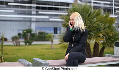 Young girl talking on mobile cell phone smiling, outdoors....