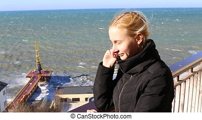 girl standing on the balcony of the sea