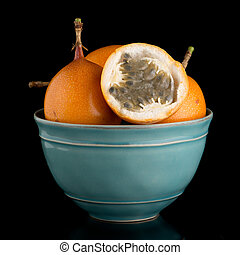 Passion fruit maracuja granadilla on ceramic blue bowl,...