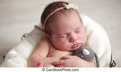 Newborn baby girl sleeping with a toy
