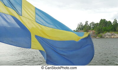 """ship with swedish flag moving in sunset, stockholm, sweden"""