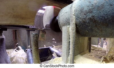 View from side of milling cutter sawing timber -...