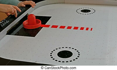 Little girl playing air hockey game with red mallet and puck...