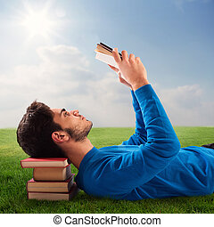 Relax with book - Boy relaxes with a book on lawn