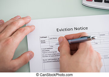 Person Hand Filling Eviction Notice Form - Close-up Of...
