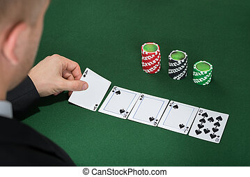 Poker Player Playing Cards On Green Table