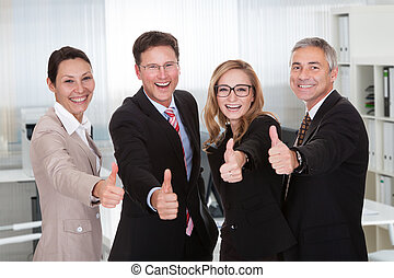 Business executives giving a thumbs up - Laughing group of...