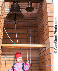 A little girl in old bronze ringing bells.
