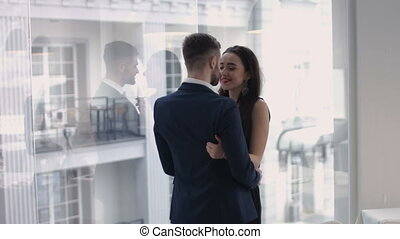 Image of young guy embracing his girlfriend and both looking through window