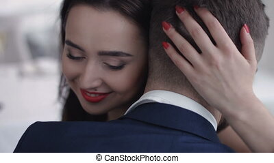Young couple embrace and hold each other. Girl looks wistful and a little sad.