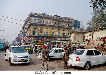 NEW DELHI, INDIA - 27 December 2011: Busy Main Bazar street, the most famous market district of Delhi(Paharganj). Cars, people and motorbike chaos.