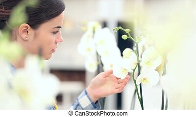 woman in garden of flowers, touches and smells an orchid