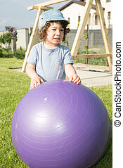 Toddler boy playing with big ball outside in garden