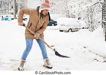 Woman shoveling snow in parking - Happy woman showveling...