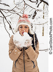 Woman blowing snow flakes - Attractive woman blowing snow...