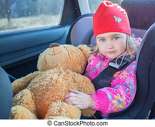 Little girl , baby in a safety car seat.
