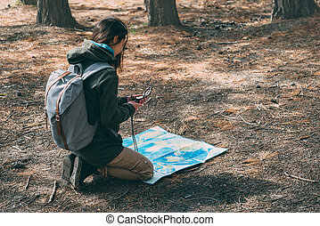 Hiker girl with a compass and map - Hiker young woman with...