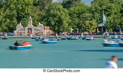 Tourists on boats at lake near Monument to Alfonso XII timelapse in the Parque del Buen Retiro - Park of the Pleasant Retreat in Madrid, Spain