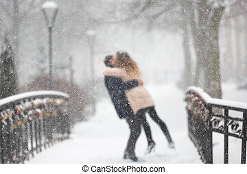 Happy couple in snowfall - Happy young couple hugging on a...