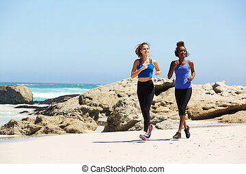 Full length two young women running on the beach