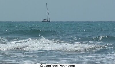 A sailboat passing in the wavy sea