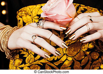 woman hands with golden manicure lot of jewelry on fancy...