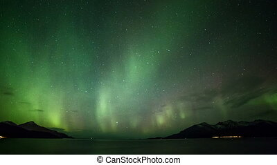 polar lights aurora borealis in a fjord in Norway in a...