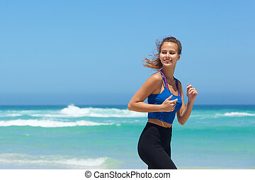 Attractive young woman running by the sea
