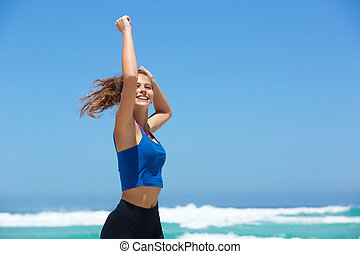 Fit young woman running by the sea with arms raised