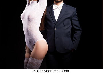 Men and woman in erotic posing on black background