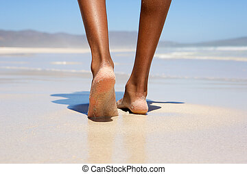 Woman walking barefoot on beach - Low angle woman walking...