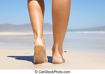 Woman walking barefoot on beach from behind - Low angle...