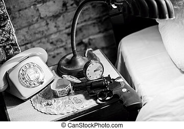 Gun on bedside table. Film Noir - Revolver sitting on...