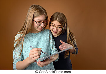 Two teen young friends using a computer tablet
