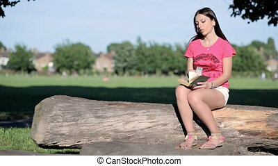 Woman sits on a log reading a book