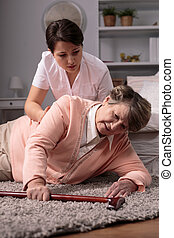 Helpful worried caregiver and senior woman on floor