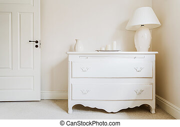 White and stylish commode with a lamp