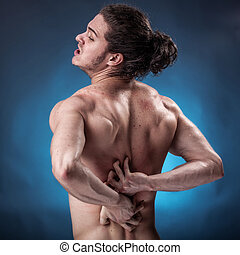 Handsome young man with back pain - Young athlete who has a...