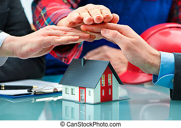 Hands saving small house with a roof