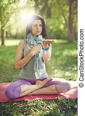 Serene and peaceful woman practicing mindful  awareness by meditating in nature with sun flare.