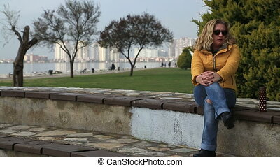 Sad lonely woman - Worried woman sitting on a city park...