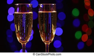 Two glasses with champagne in front of black background with...